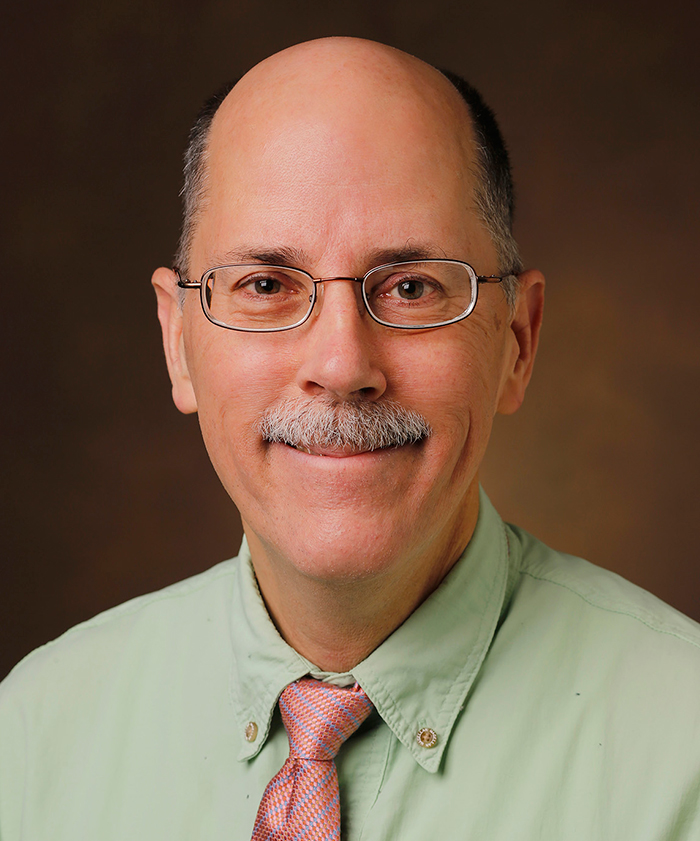 Headshot of Chuck Sanders, who is wearing a light red/pink tie with blue highlights and a green collared shirt.
