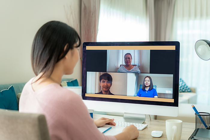 A person sitting at a desk is using a laptop to speak with three other people via a video conference.