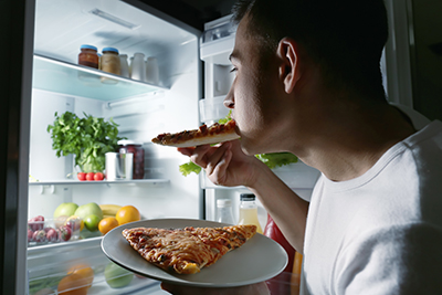Young person at an open fridge at night. They are eating a slice of pizza off a plate with another piece on it.