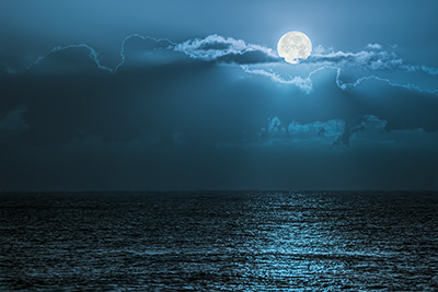 A nighttime shot of the ocean, with the moon peeking out from behind some clouds. It is shining strongly and illuminates the water.