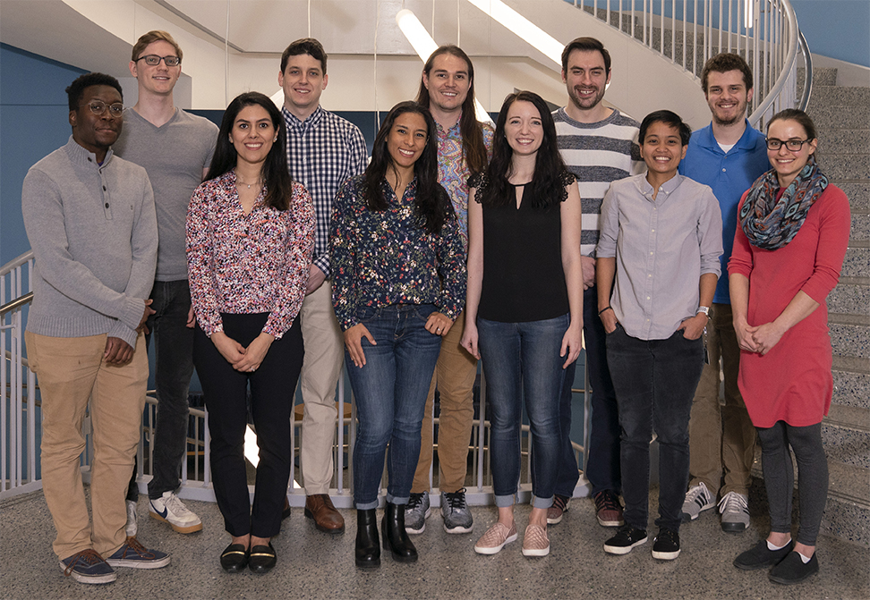 All eleven winners of the 2019 award, standing in a line, in the same order in which they are listed in the body of this webpage. They are standing in the stairwell of the Science and Engineering Building, with its white tube lights hanging above their heads.