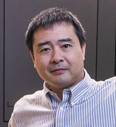Headshot of Teru Nakagawa wearing a blue-and-white vertical stripe shirt.