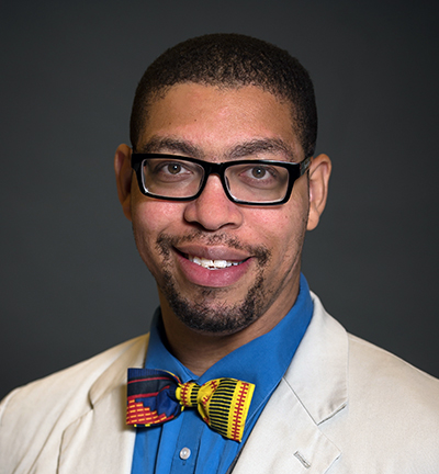 Photo of Atentor Hinton, Jr wearing glasses, a white lab coat, blue shirt, and a multi-colored tie.