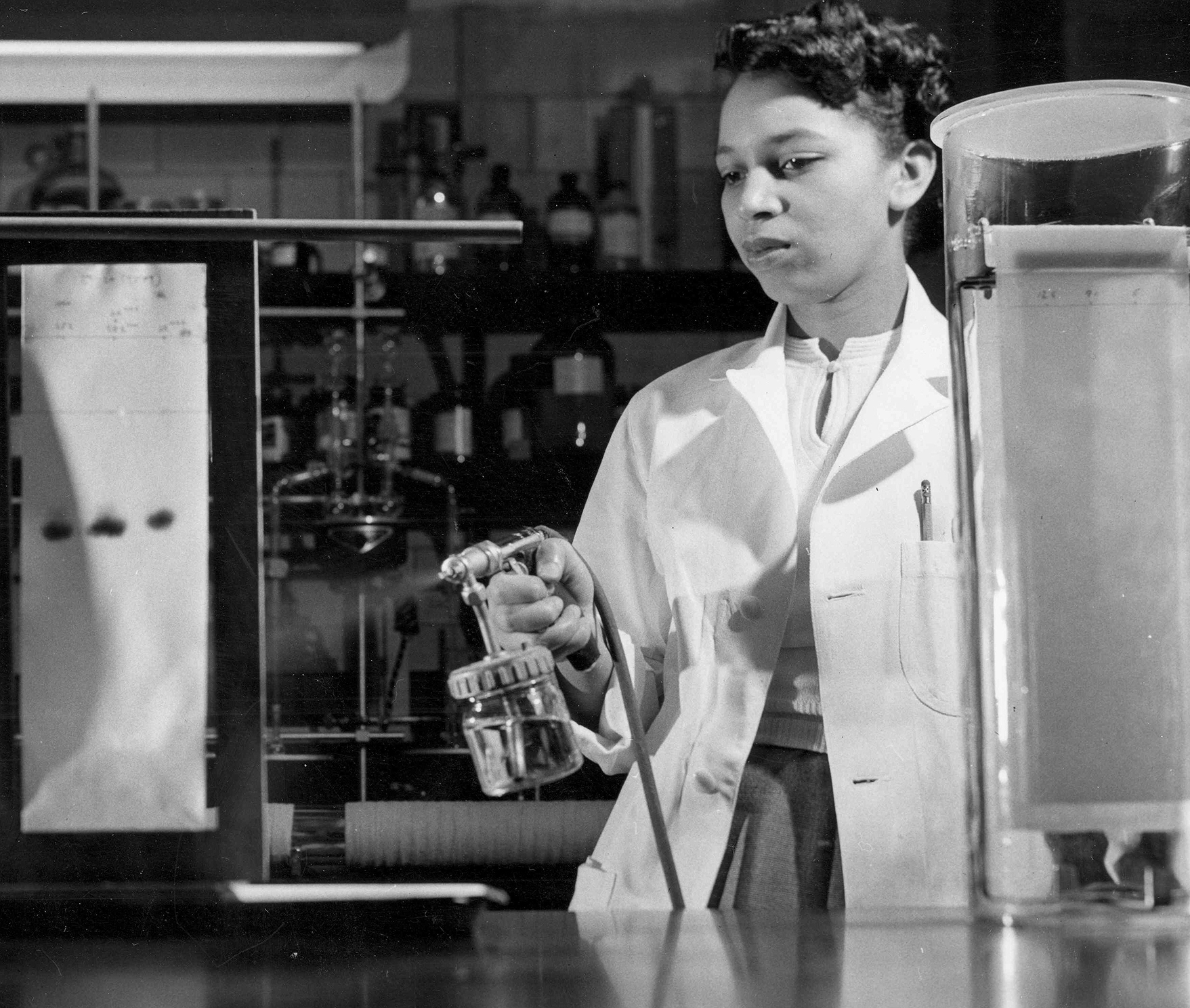 Black and white photo of Alma Levant Hayden conducting an experiment in her lab.