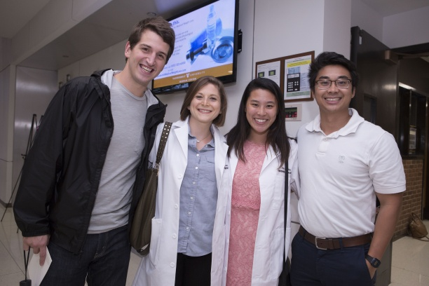 Epidemiology Ph.D. Students Lauren Saag and Jaimie Shing receive their white coats at the Simple Beginnings Ceremony