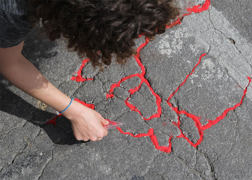 Person pouring red sand into sidewalk cracks