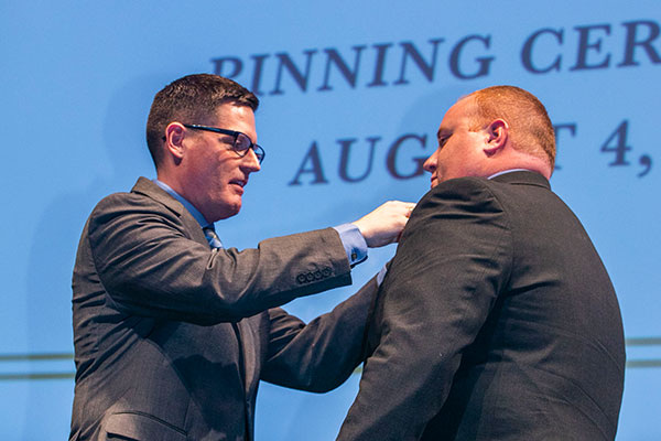 Professor Brian Widmar pins student Daniel Ford