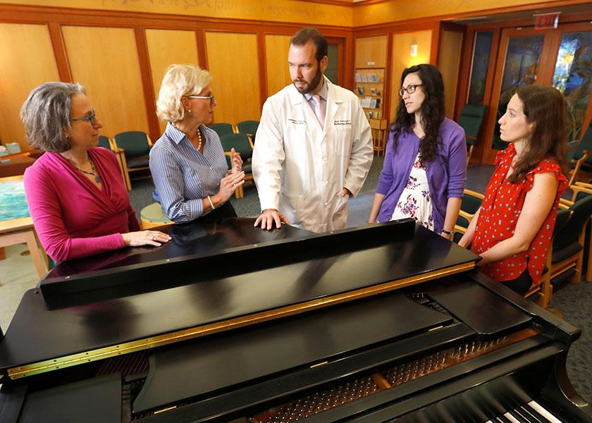 Vanderbilt researchers gathered around piano