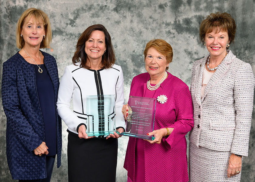 Four women in business dress with two holding big engraved glass awards. The women are Left, AACN President and CEO Deb Trautman, April Kapu, Linda Norman and AACN Board Chair Ann Cary