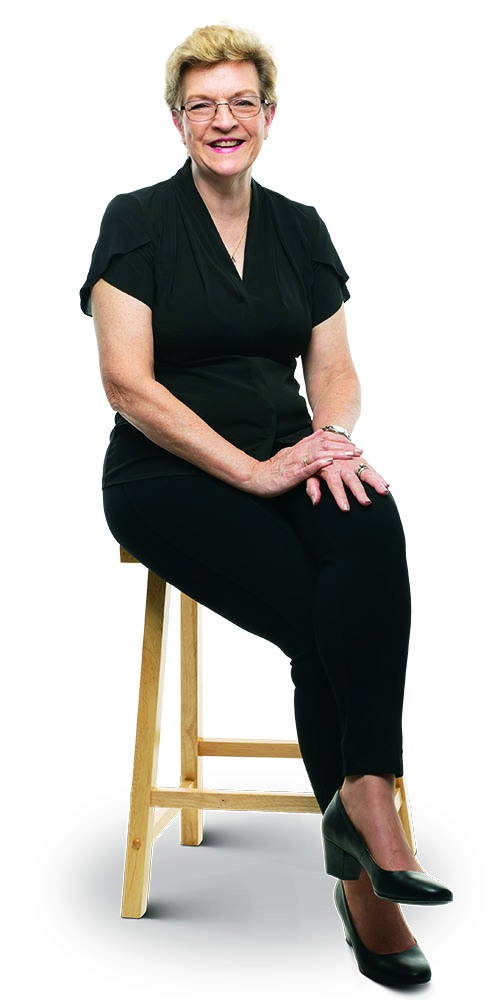 Nurse practitioner Kay Davis in black trousers and blouse, seated on a stool.