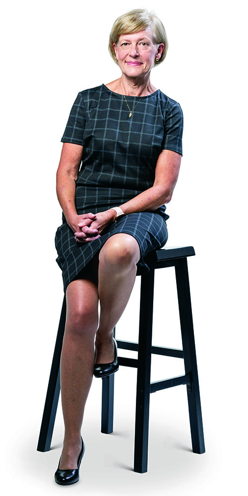 Cathy Maxwell in checked dress seated on stool.