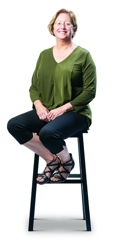 Shelagh Mulvaney in green top and dark capris, sitting on a stool.