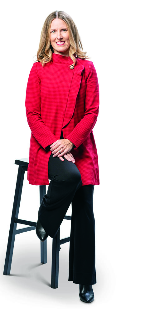 Terrah Akard in red tunic jacket and black trousers, seated on a black stool.