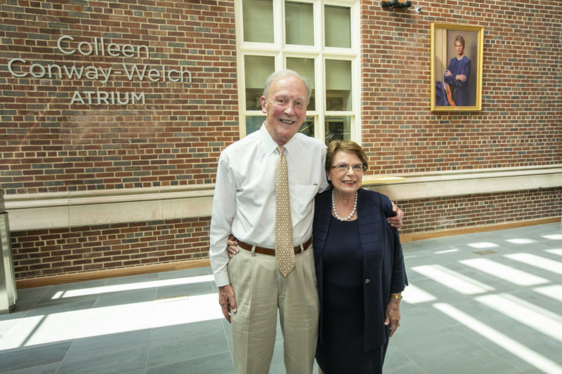 Frank Bumstead, and Dean Norman stand in front of wall in atrium with Colleen Conway-Welch portrait and name