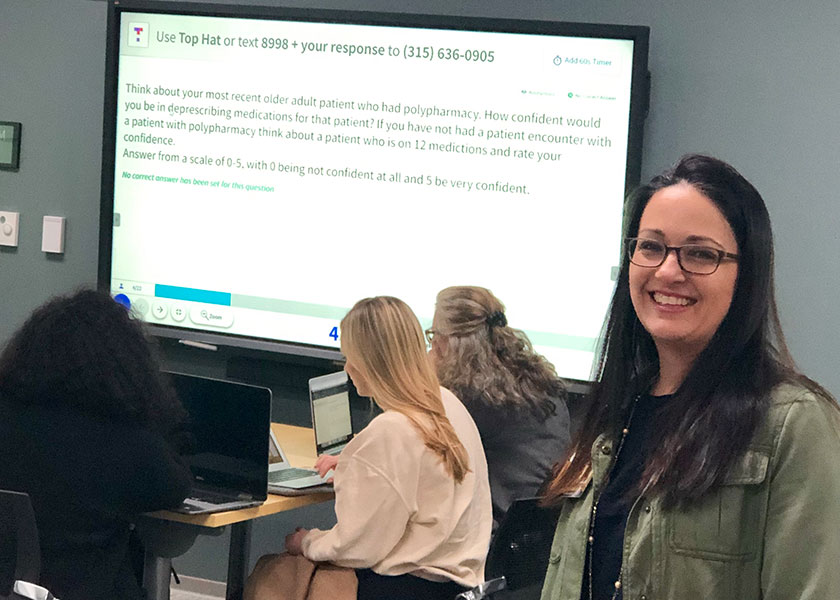 Instructor Kanah Lewallen stands in front of a large visual display that a group of students behind her are using to take a test.