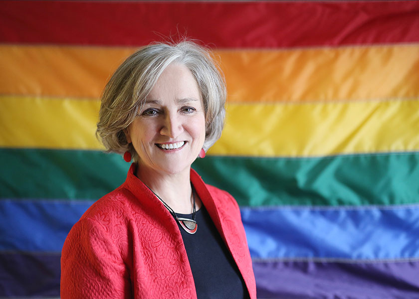 Columbia School of Nursing's Tonda Hughes in front of a rainbow flag
