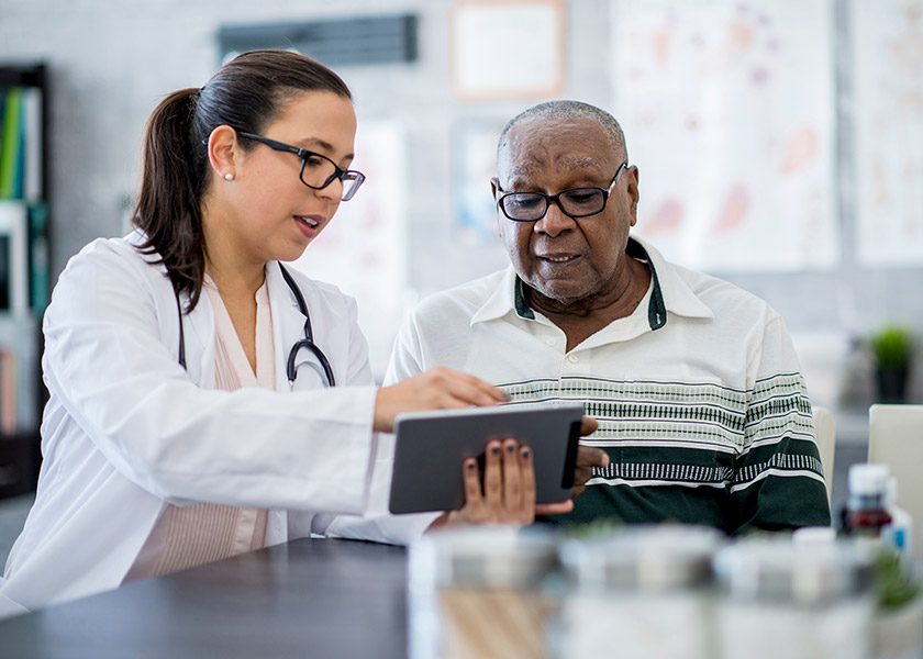 A female nurse practitioner shows something on a tablet to an older African American man