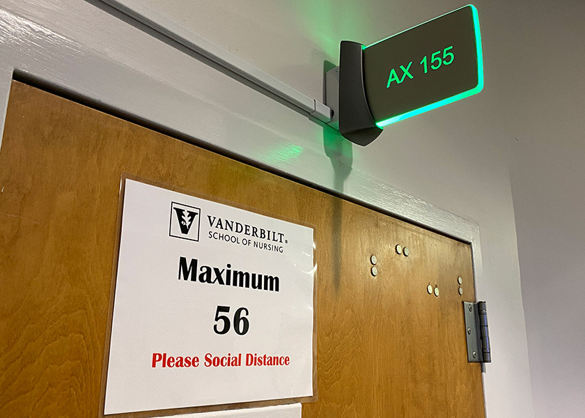 Photo of classroom with sign saying maximum occupancy is 56 people