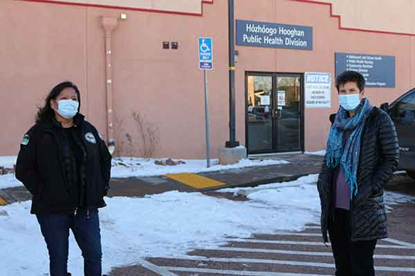 VUSN alumna Annie Moon and VUSM alumna Dr. Jill Moses in front of the health care center in Chinle, AZ, where they work. Both wear winter coats and face masks.