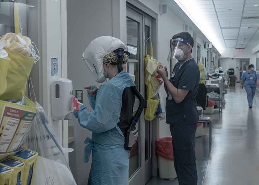 Nurse practitioner in protective gown and equipment prepares to enter a patient's room. A second health care professional is behind her, preparing to don his PPE.