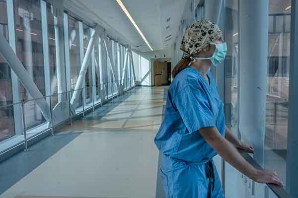 Vanderbilt School of Nursing alumna Lisa Flemmons in scrubs and mask looks out a window on the hospital's sky bridge