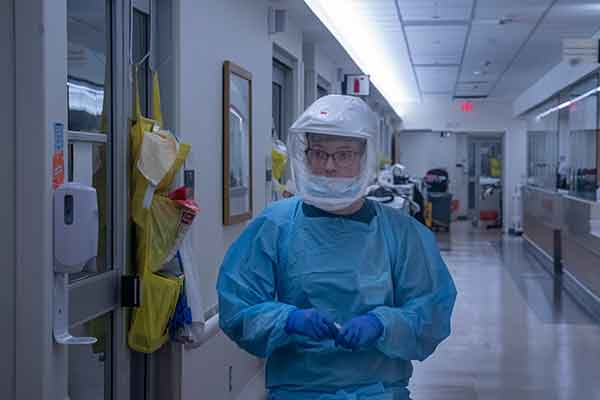 Nurse practitioner in full PPE walks down a hall in the COVID unit