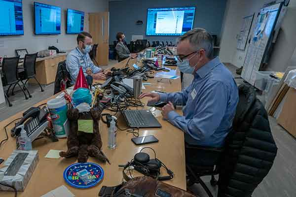 COVID command center features cluttered conference table with 3 men in masks due to COVID