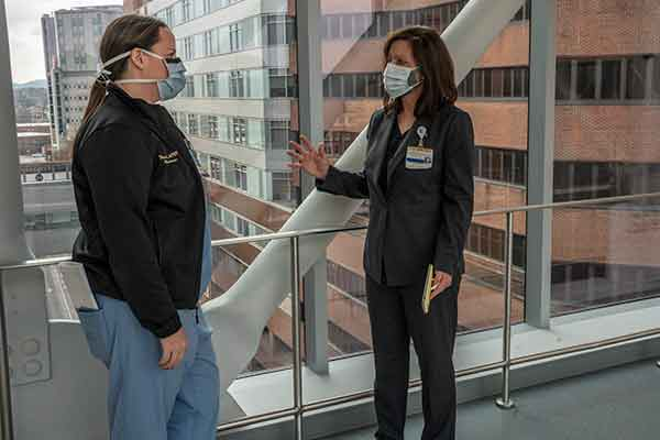 Tess Huggins (in scrubs) talks to April Kapu (in business suit) on a sky bridge. Both wear face masks.