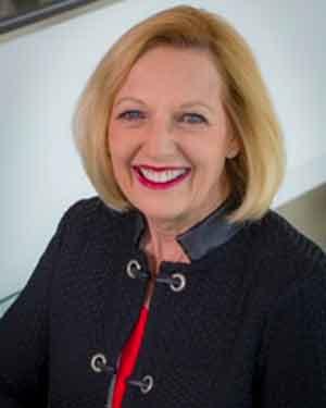 Debbie Arnow, dressed in business attire, smiles at camera