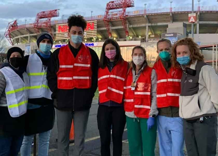 7 people in safety vests and masks stand in front of Nissan Stadium