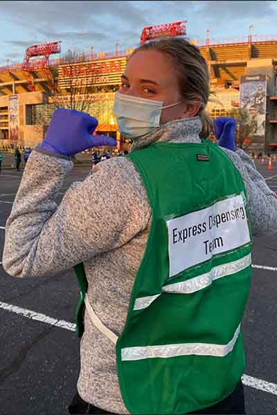 Hannah Hunt in green safety vest that reads Express Dispensary Team