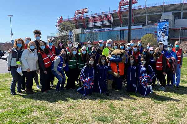 Large groups of people wearing masks and posing in front of Nissan Stadium