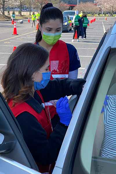 Student nurse wearing mask, vest and protective gloves gives a vaccine to a patient in a car. Behind her is another volunteer.