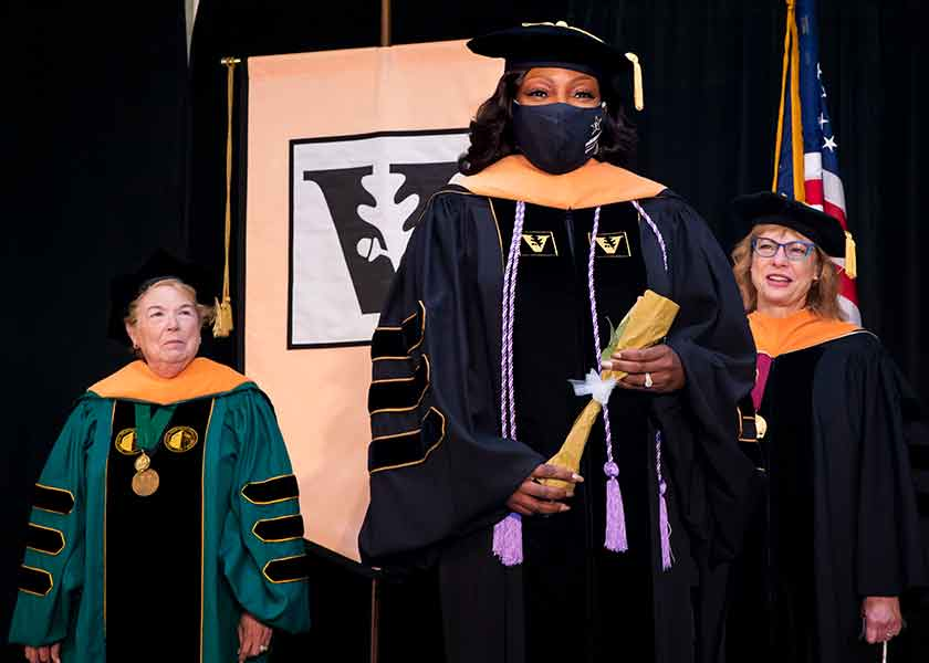 Linda Norman, graduate LaGaunda Jones, Terri Allison in academic regalia stand on stage at VUSN Commencement 2020