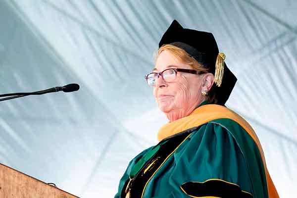 Dean Linda Norman in academic regalia at a podium