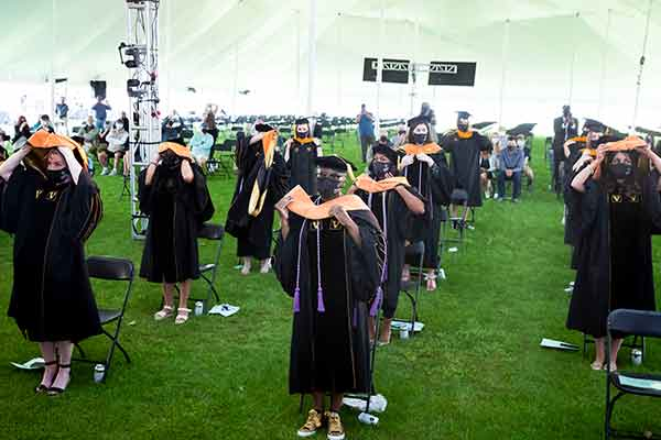 Group of graduates in academic regalia donning academic hoods