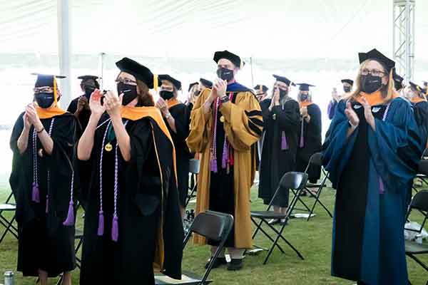 Faculty, graduates and guests give Dean Linda Norman a standing ovation