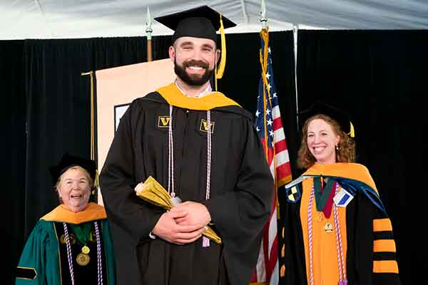 Dean Norman, MSN graduate William McConnell, Jennifer Wilbeck pose for a photo in front of the VUSN banner