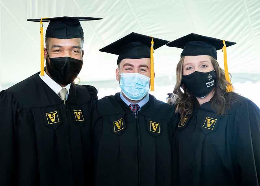 MSN graduates wearing masks and regalia. Michael Booth, Austin Rockenhaus, Ashley Allington