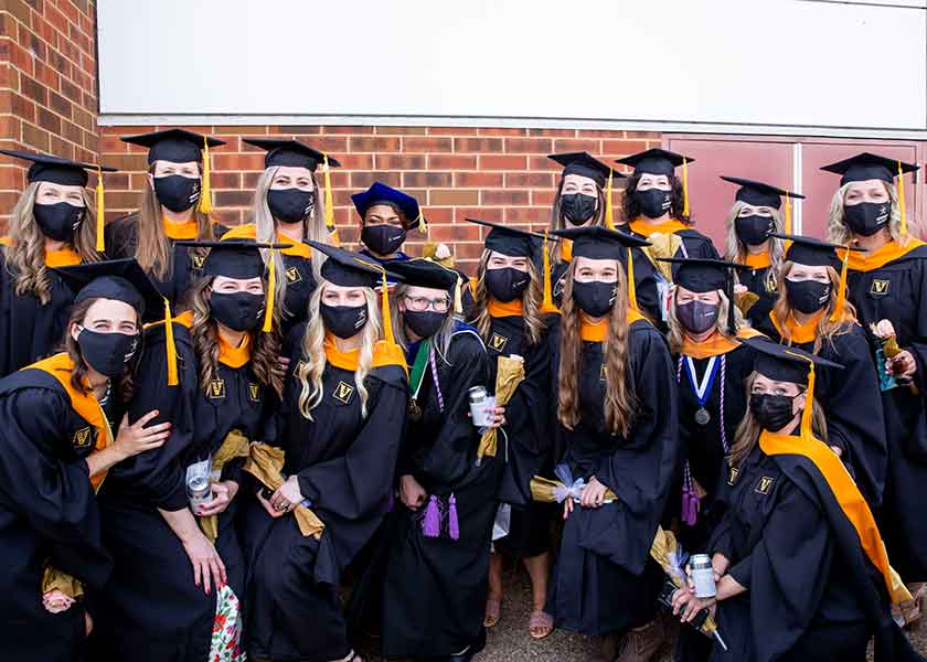 Nurse-Midwifery graduates and faculty pose after Commencement ceremonies. All are in academic robes and black masks.