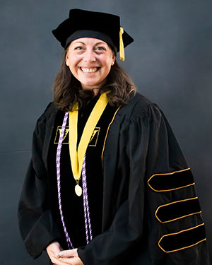 Rebecca Silvers portrait wearing fill academic regalia with VUSN Founder's Medal around her neck