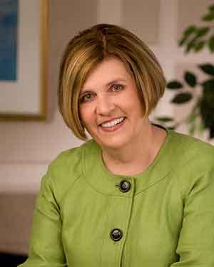 Headshot of Ann Minnick in green suit