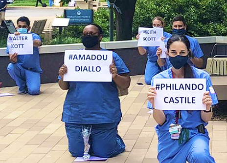VUMC workers kneel while holding BLM signs.