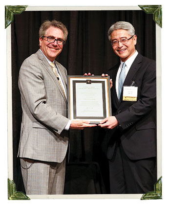 Dean Eric Johnson presenting the 2015 Distinguished Alumni Award to Heiki Miki, MBA'96
