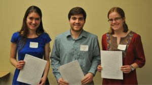 Three students pose with their writing pieces after share their work with the Undergraduate Writing Symposium audience.