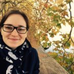 Graduate Writing Consultant Kelsey Rall is pictured standing outside wearing glasses, a black and white scarf, and blue jacket with foliage in background.