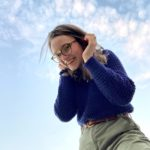 Picture of Chloe Hall wearing glasses and a blue sweater with the blue sky in the background.