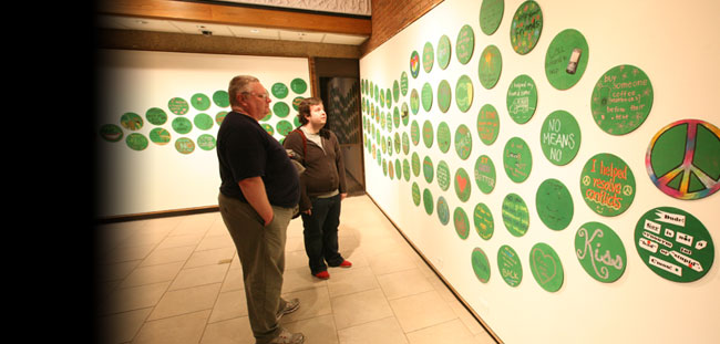 "Students viewing the ""Creating a Green Dot Campus"" exhibit in Sarratt Gallery."