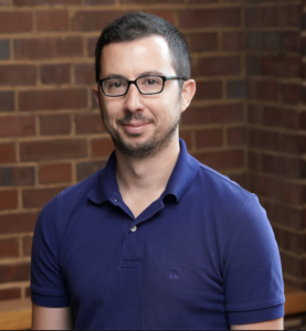 Headshot of Daniel Genkins. Subject is wearing a blue shirt and standing in front of a brick wall.