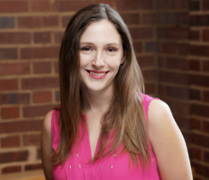 Headshot of Katherine Mckenna. Subject is wearing a pink shirt and is standing before a brick wall.
